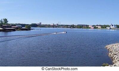 man tubing behind motorboat on river