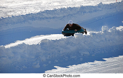 man tubing fast down the hill with snow background
