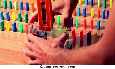 Man turn on toy machine wich begin moves and put domino ...