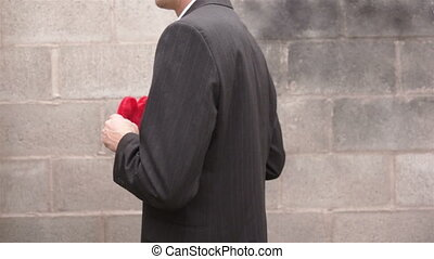 Man Turning and Holding Out Heart - Anonymous man turning...