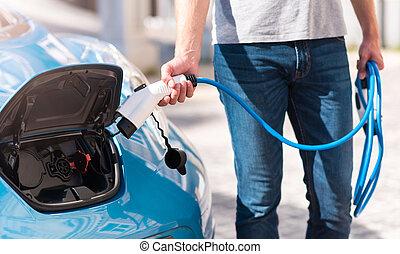 Man turning on charging of car