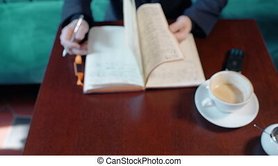 Man turning over the pages of his notebook in cafe, top...