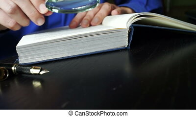 Man turning pages and read an old book with magnifier.