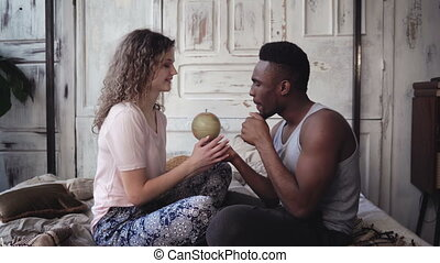 Man twist the globe, woman points with finger the location to traveling. Multiracial couple picking destination to trip.