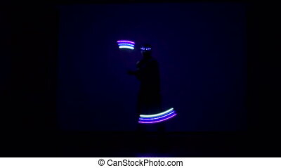 Man twists fiery circles on a light show.