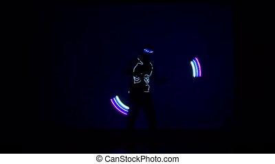 Man twists fiery circles on a light show.