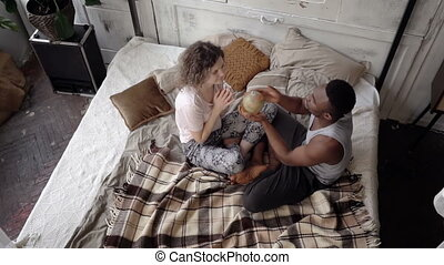 Man twists the globe, woman points the destination to travel. Multiethnic couple in pajamas rejoice and hug. Slow motion
