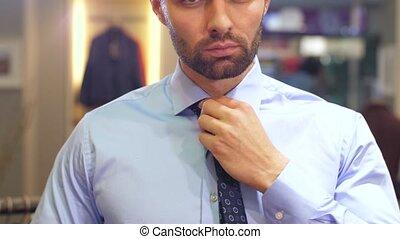 Man tying a tie at wardrobe