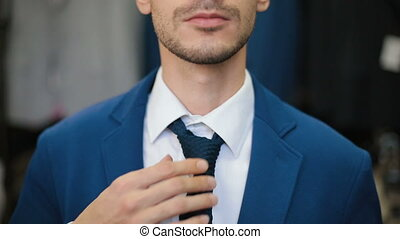 Man tying a tie at wardrobe