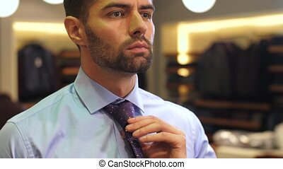 Man tying a tie at wear clothing store