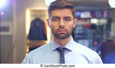 Man tying a tie at wear store