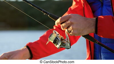 Man tying bait in fishing rod on motorboat 4k - Close-up of...