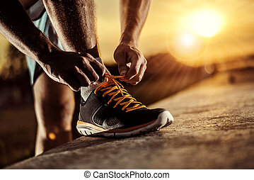 Man tying jogging shoes - A person running outdoors on a ...