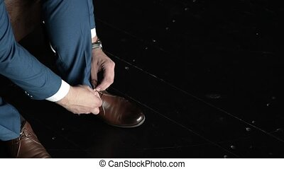 Man tying patent leather shoes. Man tying patent leather shoes formal and festive dressing. Close up