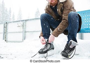 Man tying shoelace on ice skates outdoors