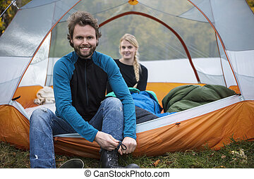 Man Tying Shoelace While Woman Relaxing In Tent
