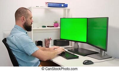 Man type on the keyboard on two monitors with the green screen. Working at home