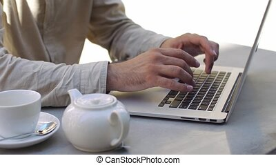 Man types something on his laptop sitting at the table in cafe