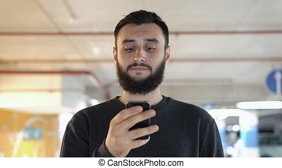 Man types something on his smartphone.
