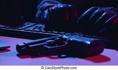 Man types the virus data, on the table there is a pistol. Close up
