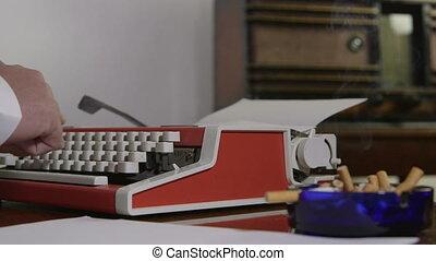 man typing on a portable typewriter
