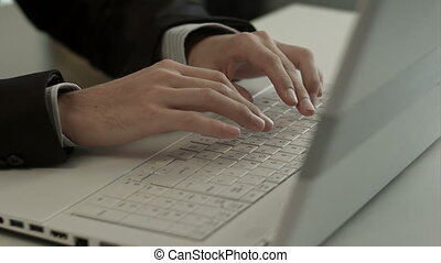 Man typing on laptop computer keyboard