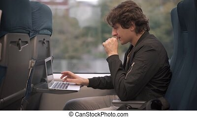 Man typing on laptop in the train - Caucasian young man with...