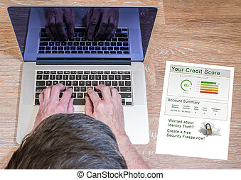 Man typing on laptop with credit report