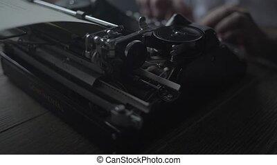 Man typing text on retro typewriter