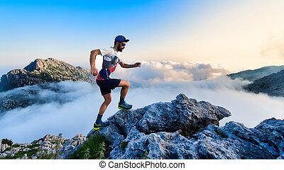 Man ultramarathon runner in the mountains during a workout