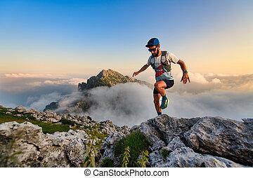 Man ultramarathon runner in the mountains he trains at sunset
