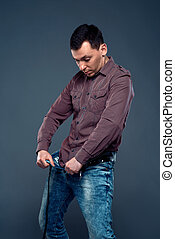 Man unbuttoned pants and looking at his penis