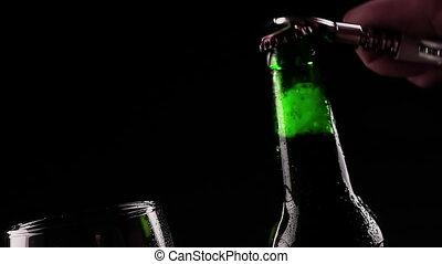 man uncap a bottle of fresh beer with foam near empty glass on black background