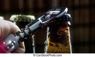 man uncap three bottles of fresh beer with foam and drops on dark background pub, slow motion