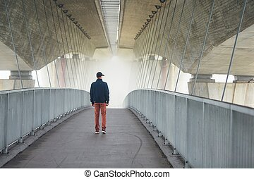 Man under highway brige in mysterious morning fog