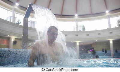 Man under water stream in the swimming pool