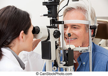 Man Undergoing a Visual Field Test - Optometrist performing...
