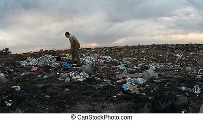 man unemployed homeless dirty looking food waste in landfill...