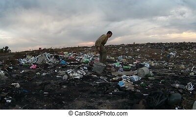 man unemployed homeless dirty looking food waste in landfill social dump video