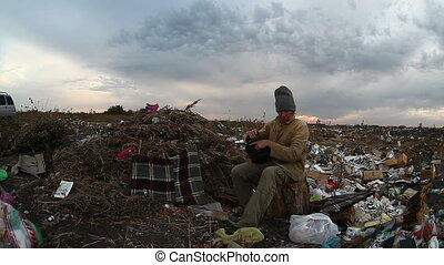 man unemployed homeless dirty looking food waste dump in...