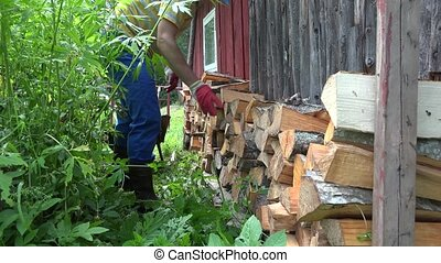 man unload neatly cut wood near wall of house in village.