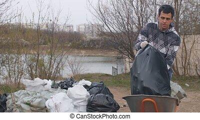 Man unloads garbage bags from wheelbarrow - Man unloads ...