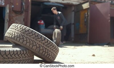 Man unloads the tires from the car trunk in garage