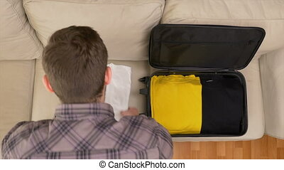 Man unpacking clothes from suitcase