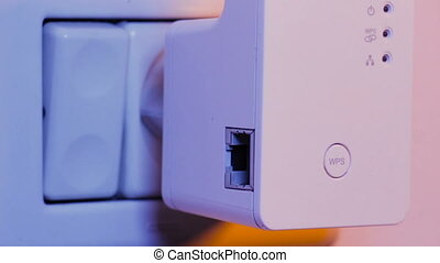 Man unplugs ethernet cable from WiFi extender device which is in electrical socket on the wall