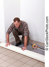 Man unrolling carpet roll