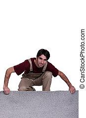 Man unrolling carpet