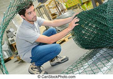 Man unrolling fencing wire