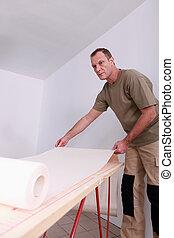Man unrolling paper