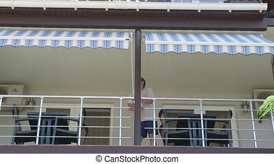 Man unrolling retractable awning on the front of hotel terrace